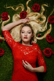 Portrait of woman in red dress laying in grass with roses Royalty Free Stock Photography