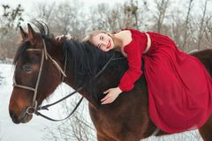 Woman in a red riding a horse. Portrait of a woman in a red dress riding a horse. Woman smiling stock image