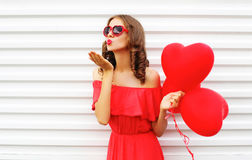 Portrait woman in red dress sends air kiss with balloon heart shape over white Stock Photo