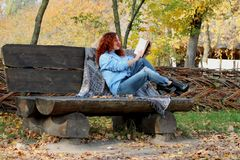 Beautiful Woman with red hair in the autumn park. sits on a bench and reads a book. Autumn background. Nearby is a warm blanket wi. Portrait of a woman with red stock photos