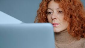 Portrait of a woman with a red hair working on a laptop. Portrait of a woman with a red hair working on a laptop stock footage