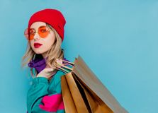 Woman in suit of 90s with shopping bags. Portrait of a woman in red hat, sunglasses and suit of 90s with shopping bags on blue and pink background royalty free stock photography