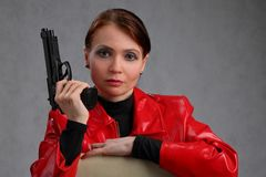 Portrait of a woman in a red jacket with a gun. Portrait of woman in red, leather jacket with gun on grey background royalty free stock image