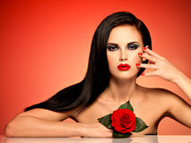 Portrait of a woman with red lips,  nails and rose in hand. Royalty Free Stock Images