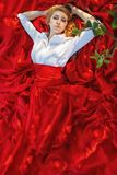 Portrait of woman in red lying under the tree Stock Photo
