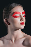 Portrait of woman with red paper eyelashes and brows posing for fashion shoot Stock Photography