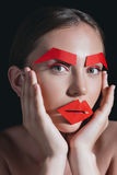 Portrait of woman with red paper lips and brows on face posing for fashion shoot Royalty Free Stock Images
