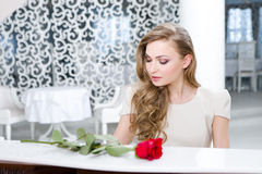 Portrait of woman with red rose playing piano Royalty Free Stock Photos