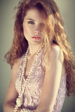 Portrait woman redhead in the sunlight. Red-haired woman in a pink dress with pearls is in sunlight Stock Photos