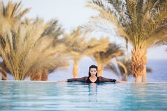 Portrait brunette woman relax in the water of infinity poolwith hands on edge luxury resort, infinity sea view. Portrait woman relax luxury pool villa, infinity royalty free stock photo