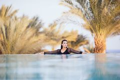 Portrait brunette woman relax in the water of infinity poolwith hands on edge luxury resort, infinity sea view. Portrait woman relax luxury pool villa, infinity stock photos