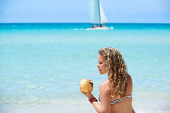 Portrait of woman relaxing with cocktail at cuban beach. Portrait of young beautiful girl at tropical beach for vacations in Varadero, Cuba, drinking cocktail in Stock Image