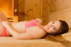 Portrait of woman relaxing in sauna. Spa wellbeing. Portrait of young woman relaxing in wooden finnish sauna. Attractive girl in bikini resting. Spa wellbeing Royalty Free Stock Photo