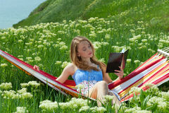 Portrait of woman resting in a hammock and reading Stock Photography