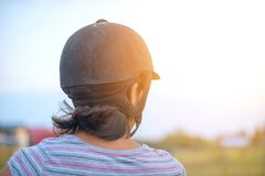 Portrait of a woman riding a horse, back view stock photo