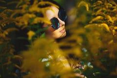 Portrait of woman in round sunglasses among nature. Beautiful girl wears stylish circular glasses royalty free stock image