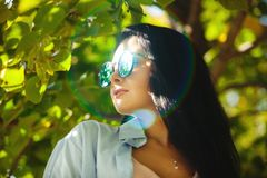 Portrait of woman in round sunglasses. Shot with glare on circular eye glasses royalty free stock image