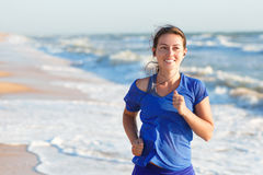 Portrait of woman running by the ocean or sea beach. Portrait of fitness woman running by the ocean or sea beach at sunrise with copy space. Running woman Royalty Free Stock Photos
