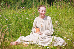 Portrait of a woman in the Russian national dress. Young woman in the Russian national dress sitting on a meadow Royalty Free Stock Photo