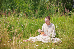 Portrait of a woman in the Russian national dress. Young woman in the Russian national dress sitting on a meadow and holding a basket of birch with black Royalty Free Stock Images