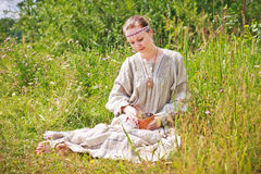 Portrait of a woman in the Russian national dress. Young woman in the Russian national dress sitting on a meadow and holding a basket of birch with black Royalty Free Stock Image