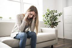 Portrait of woman with sad look on the livingroom. A Portrait of woman with sad look on the livingroom stock image