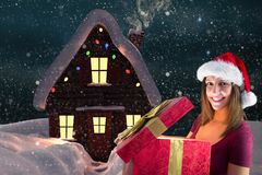 Portrait of woman in santa hat opening christmas gift. In snowfall Stock Photos