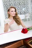 Portrait of woman with scarlet rose playing piano Stock Photo