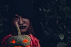 Portrait woman scary ghost in forest he has holding pumpkin. Dark tone, halloween concept royalty free stock image