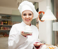 Portrait of woman selling pastry. Portrait of friendly woman with cook hat at confectionery display with pastry stock image