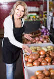 Portrait of  woman selling vegetables in grocery and smiling Stock Photography