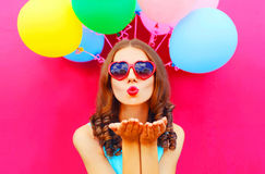 Portrait woman sends an air kiss holds an air colorful balloons on pink background Royalty Free Stock Photo