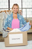 Portrait of woman separating clothes from donation box in office Stock Photography