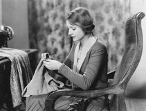 Portrait of woman sewing stock image