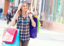 Portrait of a woman with shopping bags and telephone Stock Images