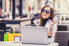 Portrait of a woman shopping on line holding a credit card and t. Happy attractive woman paying on line with a credit card and a laptop sitting in a city cafe Stock Image