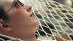 Portrait of woman with short hair wearing glasses relaxing on the hammock in her loft apartment. Stock footage Portrait of woman with short hair wearing glasses stock footage