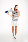 Portrait of a woman shouting in megaphone with eyes closed. Full length portrait of a young woman shouting in megaphone with eyes closed isolated on a white Stock Photography