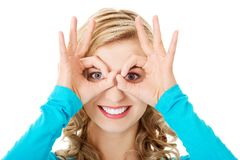 Portrait of a woman showing ok sign on eyes Stock Photo