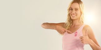 Portrait of woman showing thumbs up while pointing on pink ribbon Royalty Free Stock Image