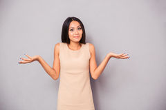 Portrait of a woman shrugging shoulders. Portrait of a young woman shrugging shoulders over gray background Royalty Free Stock Photo