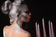 Portrait of a woman with silver bodyart and nice hairstyle keeping and blowing to candlestick with five candles in one hand Royalty Free Stock Photo