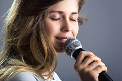 Portrait of a woman singing into the microphone. Portrait of a beautiful woman with flying hair singing into the microphone on a gray studio background royalty free stock photo