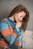 Portrait of a woman sitting on a bed and wearing a sweater Royalty Free Stock Photography