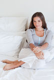 Portrait of a woman sitting on her bed Stock Photo