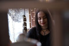 Portrait of a woman sitting near the window in cafe. Low key. Portrait of a woman sitting near the window in a cafe. Low key stock photography