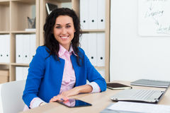 Portrait of a woman sitting in office, smiling, looking at camera. Young confident female business worker ready for the Royalty Free Stock Image