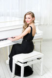 Portrait of woman sitting and playing piano Royalty Free Stock Photo