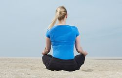 Portrait of a woman sitting on sand in yoga pose Stock Photos