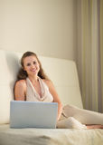 Portrait of woman sitting on sofa with laptop Stock Photos